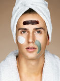 Handsome man with three different face masks chocolate, cream and clay masks Stock Photos