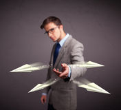 Handsome man throwing origami airplanes Royalty Free Stock Image