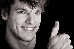 Handsome man with thumb up. Black and white portrait of handsome young man with thumb up, studio background Stock Photography