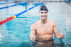 Handsome man with thumbs up in the water. At the pool Royalty Free Stock Images