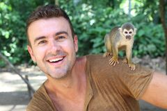 Handsome man with titi monkey on his shoulder stock photo