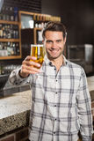 Handsome man toasting with a pint. In a pub stock images