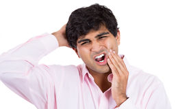 Handsome man with tooth ache and headache touching face and head Stock Images