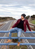 Handsome man at the top of a bridge over a highway Stock Photos