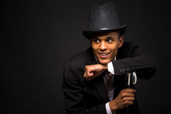 Handsome man in top hat posing with cane. Handsome actor man in top hat posing with cane isolated on black background. Happy smiling man looking away Stock Image