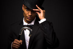 Handsome man in top hat posing with cane. Close-up portrait of handsome man adjusting black top hat. Attractive asian man in black business suit posing with cane Stock Image