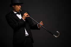 Handsome man in top hat posing with cane. And dreaming that he is using saxophone isolated on black background Royalty Free Stock Images