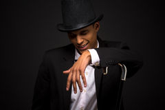 Handsome man in top hat posing with cane. Isolated on black background. Attractive man singing favourite songs in studio royalty free stock photography