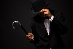 Handsome man in top hat posing with cane. Portrait of handsome man adjusting his top hat in studio. Asian man in business suit posing with cane Stock Images