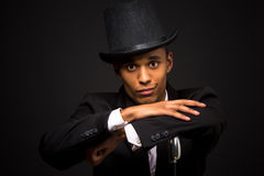 Handsome man in top hat posing with cane. Portrait of handsome man in business suit posing. Asian man in top hat posing with cane in studio stock images