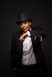 Handsome man in top hat posing with cane. Portrait of happy man in top hat leaning on the cane. Attractive asian man in business suit posing in studio Royalty Free Stock Photos
