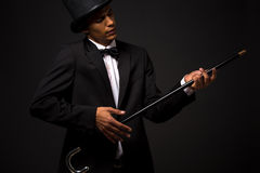Handsome man in top hat posing with cane. Portrait of handsome man in top hat holding cane and dreaming or imagining that he is playing the guitar royalty free stock photos