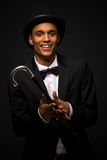 Handsome man in top hat posing with cane. Portrait of handsome man in top hat smiling for the camera and holding cane isolated on black background stock photo