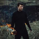 Handsome man with a torch in his hands sets fire to the grass in. A handsome man with a torch in his hands burns. The guy brings trouble to nature. Ecology Stock Photo