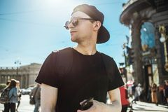 Handsome man tourist with phone. Young man standing on a street of european city. Navigation, travel concept.  royalty free stock photos