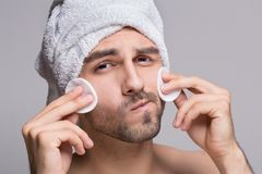Handsome man with towel on head cleaning face royalty free stock images
