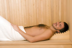 Handsome man in a towel relaxing in sauna Stock Photography