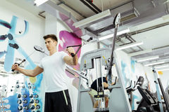 Handsome man training in clean modern gym. On various machines Stock Photography