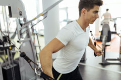 Handsome man training in clean modern gym. On various machines Stock Images