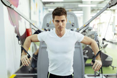 Handsome man training in clean modern gym. On various machines Stock Photos