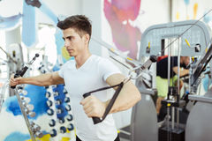 Handsome man training in clean modern gym. On various machines Stock Image