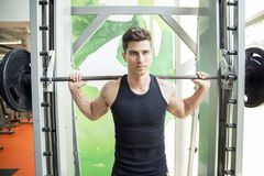 Handsome man training in gym stock image