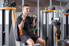 Handsome man training on modern machine and working out in gym Stock Image