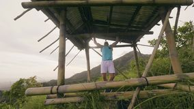 Handsome man training pull up exercise on wooden crossbar outdoor. Athlete man exercising pull ups on green hill