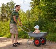 Handsome man transporting little baby. Handsome men transporting little baby using wheelbarrow Stock Images