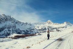 Handsome man travel in winter mountains with camera Stock Images