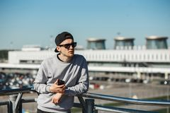 Handsome man traveler with phone near airport Pulkovo in Saint-Petersburg. He clothed in round sunglasses, black cap and stock photo