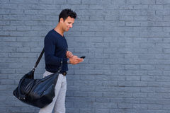 Handsome man traveling with bag and cell phone. Side portrait of a handsome man traveling with bag and cell phone Royalty Free Stock Photo