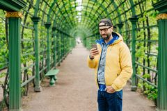 Handsome man in trendy cap, jeans and yellow anorak wearing eyeglasses holding his hand in pocket communicating online with his fr. Iend while standing against stock photography