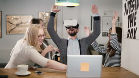 Handsome man tries app for VR helmet virtual reality glasses his friends and colleagues supporting him in modern office