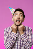 Handsome man trying to take off birthday hat over purple background. Stock Photography