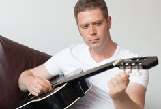 Man tuning a guitar. Stock Photo