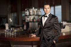 Handsome man in tuxedo at bar holding whisky stock photography
