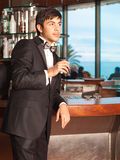 Handsome man in tuxedo at bar holding whisky glass stock photo