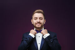 Handsome man in tuxedo and bow tie looking at camera. Fashionable, festive clothing. emcee on dark background Royalty Free Stock Photography