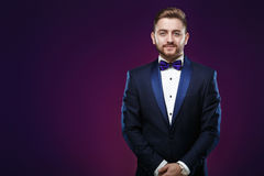 Handsome man in tuxedo and bow tie looking at camera. Fashionable, festive clothing. emcee on dark background Stock Photos