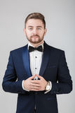 Handsome man in tuxedo and bow tie looking at camera. Fashionable, festive clothing. emcee on grey background Stock Images
