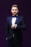 Handsome man in tuxedo and bow tie looks at watch. Fashionable, festive clothing. emcee on dark background Stock Photos