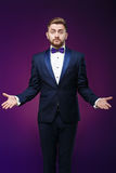 Handsome man in tuxedo and bow tie is surprised, throws his hands. compere in fashionable, festive clothing Stock Image