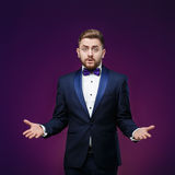 Handsome man in tuxedo and bow tie is surprised, throws his hands. compere in fashionable, festive clothing Royalty Free Stock Photo