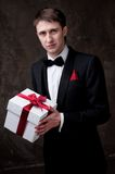 Handsome man in tuxedo with a gift box Royalty Free Stock Photography