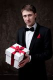 Handsome man in tuxedo with a gift box Royalty Free Stock Images