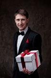 Handsome man in tuxedo with a gift box Stock Photography