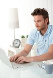 Handsome man typing on laptop computer. Keyboard, looking at screen, smiling stock image