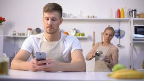Handsome man typing message in phone, jealous wife peeking, cheating in marriage. Stock footage stock video footage