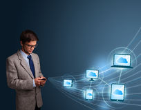 Handsome man typing on smartphone with cloud computing Royalty Free Stock Images